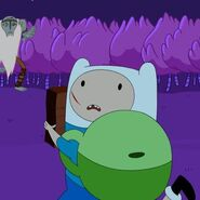S4e26 Finn looking back holding The Enchiridion