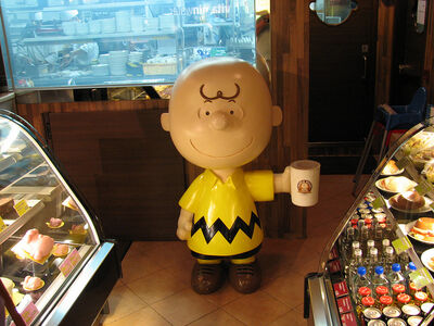 Statue of the cartoon character Charlie Brown holding a huge coffee mug on display in a Charlie Brown Cafe in Hong Kong.