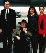 This picture shows, from left to right, President George Bush, Doris, Debra and Patti Tate. All but Doris Tate are standing in a row facing the camera. Doris Tate, who was ill with brain cancer, is in a wheelchair; Debra stands beside her, holding her hand.