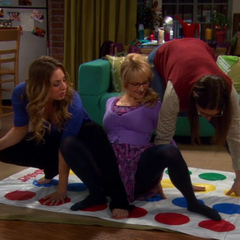 The girls playing Travel Twister while Penny drinks at the same time.