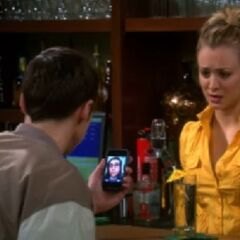 Amy video calls Sheldon after reading his Facebook post as he is at The Cheesecake Factory bar with Penny