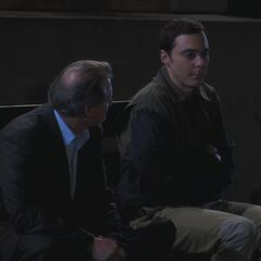 Sheldon talking to a guy at a bus stop.