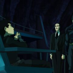 Damian, Alfred and Batman in the Batcave.