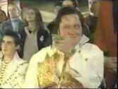 Elvis impersonator winks at Ash
