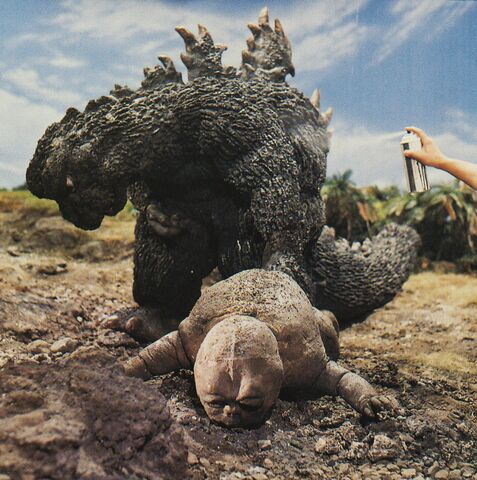 File:SOG - Spraying Godzilla While He Drags Baby Minilla.jpg
