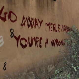Writing on the back wall, telling Merle to go away, and that he is a