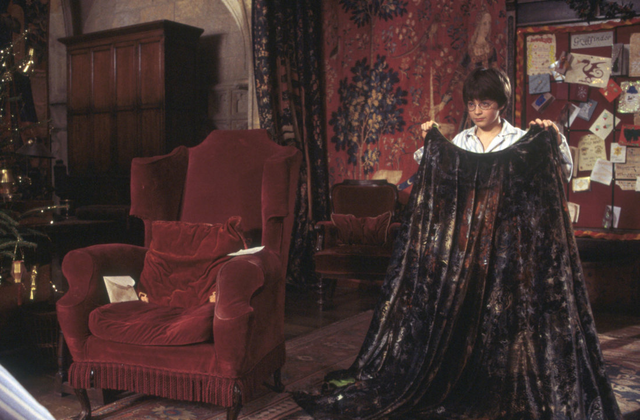 File:HarryHoldingInvisibilityCloakInGryffindorCommonRoom.png