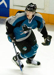An ice hockey player skating in mid-stride. He holds his stick with one hand along the ice while looking to his right. He wears a teal jersey with black trim, as well as a black, visored helmet.