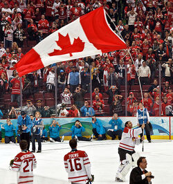 A helmetless ice hockey goaltender carrying a large Canadian flag by its pole over his head as teammates, spectators and media look on. He is wearing a white and red jersey with white pads.