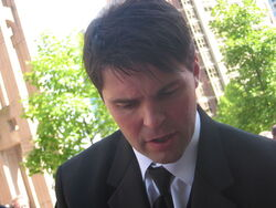 Jagr, a caucasian man with short, brown hair, has his head turned down slightly and is wearing a black suit and tie with a white dress shirt.