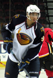 Hockey player in white and black uniform, with a picture of a bird's head in the middle. He leans forward slightly, holding his stick.