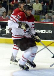 Hockey player in white and red uniform. He jumps slightly above the ice, holding his stick.