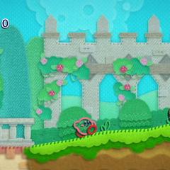 Kirby caminando por un nivel del juego cerca a un Waddle Dee.