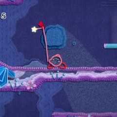 Kirby usando su habilidad de hilo para quitar un parche de la pared.