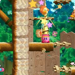 Kirby usando su habilidad de erizo para dañar a un Waddle Dee.