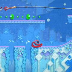 Kirby transformado en un trineo en una zona de nieve.