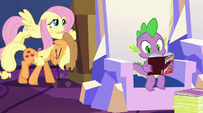 AJ and Fluttershy pushing a box while Spike reads a Daring Do novel EG2