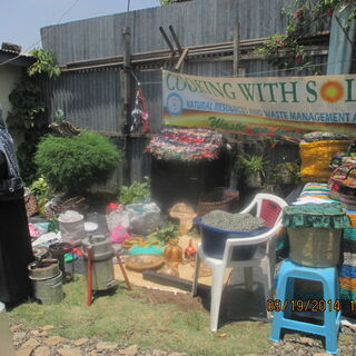 Mama solar of NAREWAMA displays fireless cookers, energy saving stoves, and recycled plastic wastes to guests at her home.