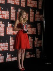 A young woman with blond, curly hair, in left profile, holds up an award. She is dressed in a red dress while standing on the red carpet.