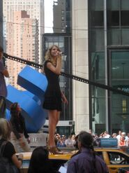 A young woman with blond, curly hair looks up while being dressed in a black cocktail dress and standing on a taxi cab.