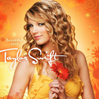 A female with curly blond hair looks forward in a semi-right profile pose. She holds a flower against her chest, which is clothed by a yellow blouse. The background alternates between different yellow and orange values while hosting floral patterns.