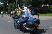 Gendarmerie motor officer raising arm in traffic