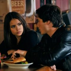 Elena and Damon eating together.