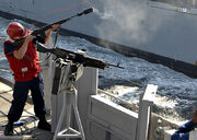 US Navy 090107-N-3392P-065 Gunner's Mate Seaman James Clarke fires a shot line to the Military Sealift Command dry cargo-ammunition ship USNS Lewis and Clark (T-AKE 1)