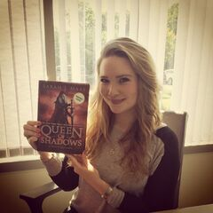 Sarah with a copy of <i>Queen of Shadows</i>