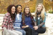 1239136-767175-group-of-four-teenage-girls-sitting-on-bench-in-autumn-park