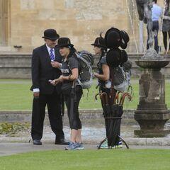 Kym & Alli receiving Bowler Hats and Umbrellas in Leg 2.