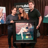 Ariana holding platinum certificate for problem