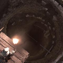 Ezio staat voor een put.