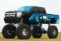 Blue and black jacked up truck with skull on the side