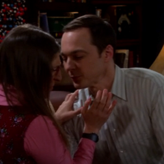 Sheldon wants to kiss her. Amy stopping it.