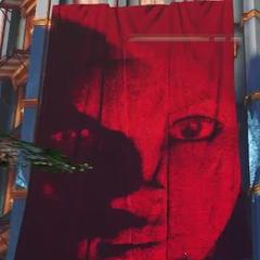 La cara de Daisy proyectada en una serie de telas rojas.