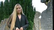 Chloë stands next to the carved tombstone