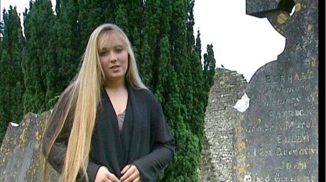 File:Chloë stands next to the carved tombstone.jpg