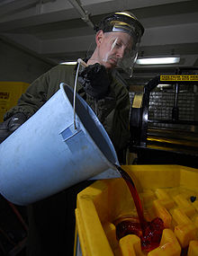 220px-US Navy 090316-N-6597H-004 Boatswain's Mate 2nd Class George Cabeen empties used hydraulic fluid into a storage container