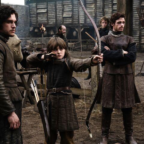 Рикон Старк (за Роббом) смотрит как его брат Бран стреляет из лука, эпизод