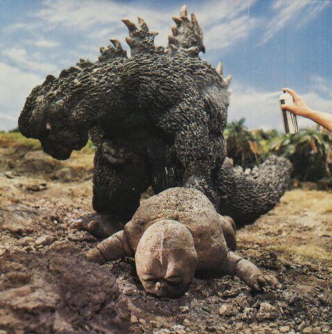 File:SOG - Spraying Godzilla While He Drags Baby Minilla.jpg