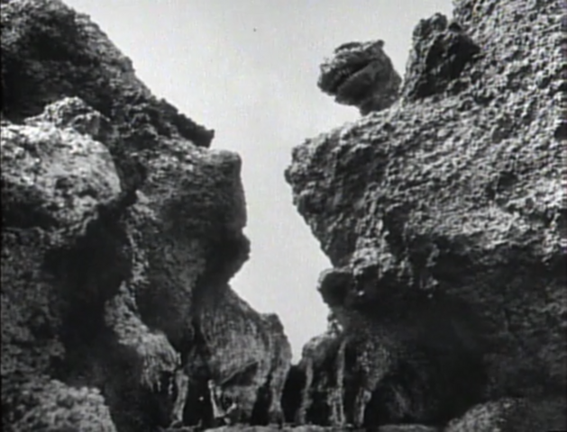 File:Godzilla Raids Again - 1 - Godzilla peering down from over the mountains.png