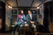 Andy Karl and Carlyss Peer in-character on a bed