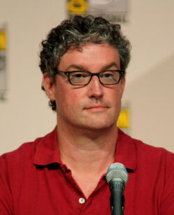A man with glasses and a red shirt is sitting in front of a microphone.