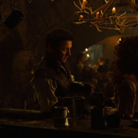 Hansel speaks to a woman in the tavern.