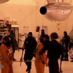 A hooded Hiro and Tracy are being led while, in the background, Nathan is carrying Claire to his car in the background to release her.