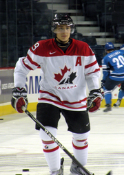 Hockey player in white Canada uniform. He stands on the ice, hands by his side, one holding his stick.
