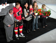 A man in a red hockey uniform accepts a silver stick from another man in in a grey suit as his wife and three young daughters stand beside.