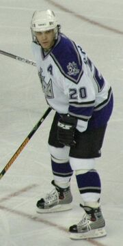 Hockey player in white and blue uniform. He stands shoulder-width apart and stands in a readied stance.