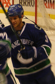 An ice hockey player in the midst of skating and holding his hockey stick upwards. His equipment is coloured blue and green.